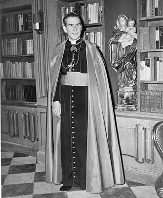Fulton J. Sheen - Bishop Sheen stands before a bookcase on the set of his Dumont television program