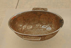 A Tang era gilt-silver ear cup with flower design, found from a 1970 excavation in Xi'an. Gilt silver eared cup.jpg