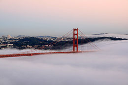 A red suspended bridge just above clouds