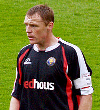 A man wearing a black, red and white football shirt.