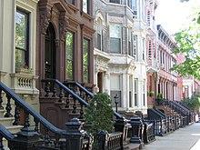 Vista de uma rua com casas geminadas em marrom, branco e vários tons de vermelho.