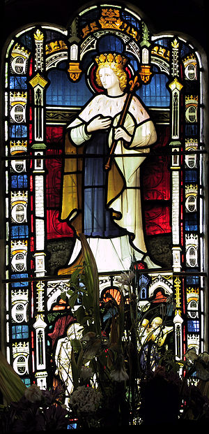 Greensted Church - A stained glass window depicting St Edmund, visible inside the church.