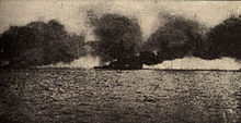 Large ship at sea billowing dark smoke
