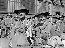 Two Maori men wearing military uniforms smile at the camera, surrounded by other soldiers in front of a building