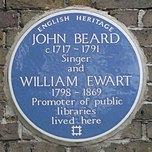 "A Blue plaque on a brick wall with the words ""John Beard C1717 - 1791 Singer and William Ewart 1798 - 1861 Promoter of Public Libraries"