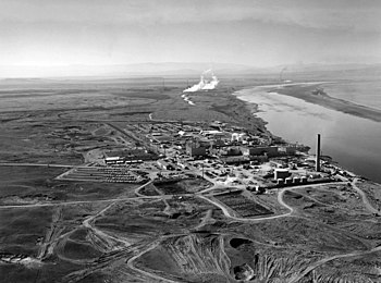 Nuclear reactors line the riverbank at the Hanford Site along the Columbia River. The N-Reactor is in the foreground, with the twin KE and KW Reactors in the immediate background. The historic B-Reactor, the world's first plutonium production reactor, is visible in the distance.
