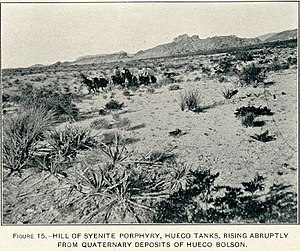Hueco Tanks - US Geological Survey photograph shows a wagon crossing the desert in front of Heuco Tanks in 1909.