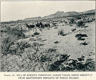 Hueco Tanks - US Geological Survey photograph shows a wagon crossing the desert in front of Hueco Tanks in 1909.