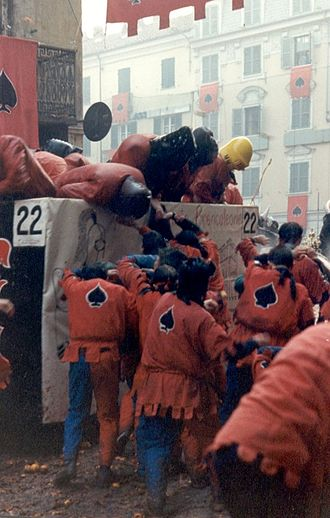 Battle of the Oranges - The Asso di Picche, founded in 1947 and wearing a black Ace of Spades on red, is the oldest of the nine pedestrian teams of orange throwers that partake in the Battle of the Oranges. Here they battle against one of the approximately forty Aranceri Carri da Getto – orange-throwers in carts.