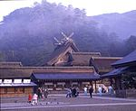 A large wooden building with gabled roof and forked roof finials located beyond other buildings.