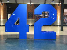 An eight-foot blue sculpture of a stylized uniform number, 42, set atop a polished interior walkway
