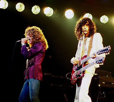 The British rock band Led Zeppelin was one of the most popular and influential bands of the 1970s. The band's heavy, guitar-driven sound has led them to be cited as one of the progenitors of heavy metal. Jimmy Page with Robert Plant 2 - Led Zeppelin - 1977.jpg