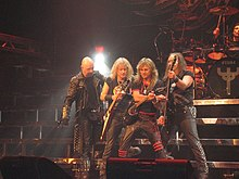 The band Judas Priest are onstage at a concert. From left to right are the singer, two electric guitarists, the bass player, and the drummer, who is seated behind a drumkit. The singer is wearing a black trenchcoat with metal studs.