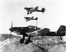 Black and white photograph of aircraft flying with mountains in the background