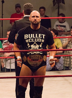 IWGP Tag Team Championship - Karl Anderson, four-time IWGP Tag Team Champion, with one of the title belts in May 2014