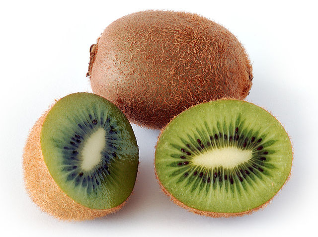 A whole and a cut kiwifruit.