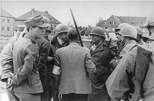 Dachau liberation reprisals - SS men confer with General Henning Linden during the capture of the Dachau concentration camp. Pictured from left to right: SS aide, camp leader Untersturmführer Heinrich Wicker (mostly hidden by the aide), Paul M. G. Lévy, a Belgian journalist (man with helmet looking to his left), Dr. Victor Maurer (back), Gen. Henning Linden (man with helmet, looking to his right) and some U.S. soldiers.