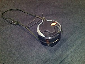 M14 mine - M14 mine with safety clip fitted. The U-shaped safety clip (with green pull-cord attached) and location of the yellow arrow on the pressure plate indicate that this mine has not been armed