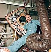 Photographie couleur de Collins assis sur l'écoutille de son module et tenant le panneau ouvert.
