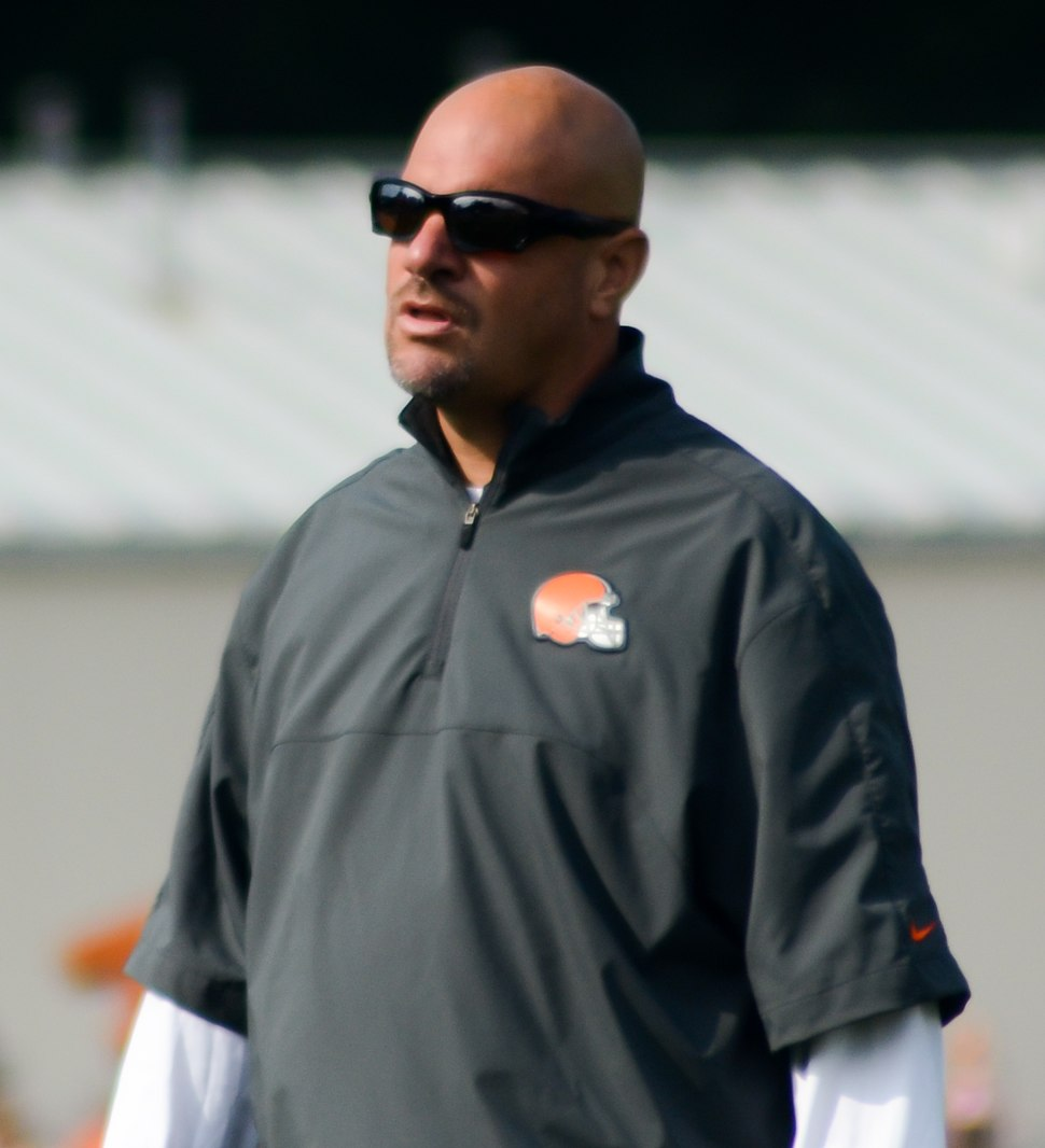 Candid waist-up photograph of Pettine wearing a grey pullover bearing a Cleveland Browns logo and dark sunglasses standing on a football field