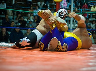 Canek (wrestler) - Canek (in blue and yellow) wrestles one of his more frequent rivals, Mil Máscaras (in silver and black), in 2009.