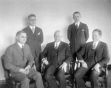 A black-and-white photo of five men wearing business attire. Two are standing and three are seated.