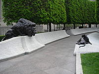 Short white walls with an adult lion sculpture sitting on the left and a lion cub on the right