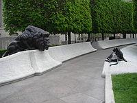 Krátké bílé stěny se sochou dospělého lva vlevo a levím mládě vpravo