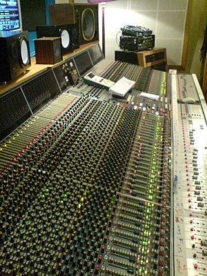 Recording studio - Neve VR60, a multitrack mixing console. Above the console are a range of studio monitor speakers.