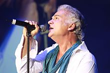 A profile shot of a man with wavy grey hair performing on stage with a black microphone. He is wearing a white shirt and a teal scarf.