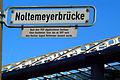 Noltemeyerbrücke Hannover Straßenschild mit gesondert angebrachter Informationstafel zum 1959 abgebrochenen Gasthaus Klein-Buchholzer Turm ab 1897 nach August Noltemeyer benannt.jpg