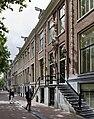 Overzicht voorgevel met dubbele ingangspartij, zandstenen kelderpui en middenrisaliet met een beeld van St. Michael en de draak - met straatbeeld - Amsterdam - 20536140 - RCE.jpg