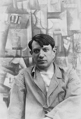 Picasso in front of his painting The Aficionado (Kunstmuseum Basel) at Villa les Clochettes, summer 1912 Pablo Picasso, summer 1912.jpg