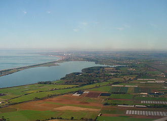 "Pontine Marshes - National Park of Circeo, on the coast of the Pontine Fields: The view is an aerial photograph. Visible in the foreground is Lago di Fogliano, one of the laghi costieri, ""coastal lagoons""."