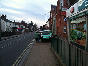 Overspill parking - Pedestrians walk close to carriageway to pass cars parked on the pavement; double yellow lines mean 'no waiting'