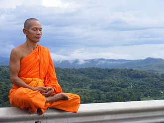 Theravada - Theravādin monk meditating while seated in the Lotus position beside Sirikit Dam (Thailand)