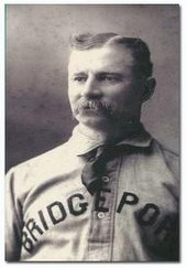 "A mustachioed man wearing a baseball jersey with ""BRIDGEPORT"" across the chest"