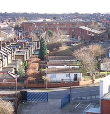 A strip of grass recedes in a straight line into the distance towards a large yellow brick building. Three single storey huts stand on the grass