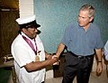 President George W. Bush shakes the hand of legendary Fats Domino, wearing a National Medal of Arts.jpg