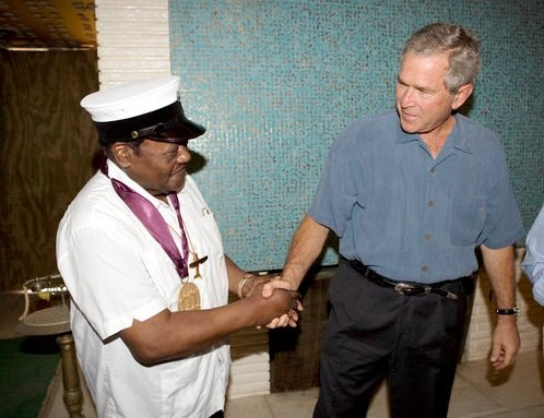 President George W. Bush shakes the hand of legendary Fats Domino, wearing a National Medal of Arts