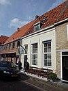 foto van Huis met gepleisterde lijstgevel onder dak, dat doorloopt over andere huizen