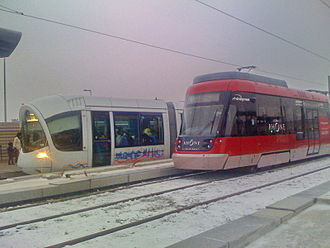 Lyon tramway - A Rhônexpress train, foreground, with a T3 tram.
