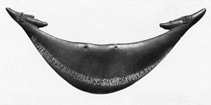 A crescent shaped piece of wood with two small heads at the tips. A line of small pictures runs the length of the crescent