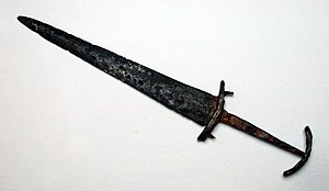 "Swiss dagger - A  basler from 14th-century Switzerland, showing the characteristic curved guard-pieces of the later Swiss dagger, but the curvature of the two pieces is parallel, while the classical Swiss dagger has opposite curvature as it were ""enveloping"" the hand."