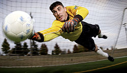 A goalkeeper dives to stop the ball from entering his goal.