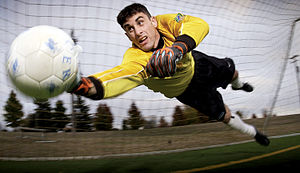 A football goalkeeper leaves the ground to parry a shot on goal
