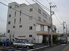 Grigio edificio di tre piani con una loggia frontestrada sormontata da una veranda chiusa