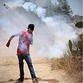 Tear gas grenade thrown back to soldiers using sling in Ni'lin during weekly Demonstration, July 2014.jpg