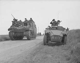 M7 Priest - M7 Priest passes by a Humber Scout Car as it moves into position to support an attack on Caen, 8 July 1944.