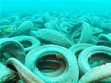 An endless bed of old, skummy tires rests piled upon the ocean's floor; a small yellow fish swims by the left of the photo.